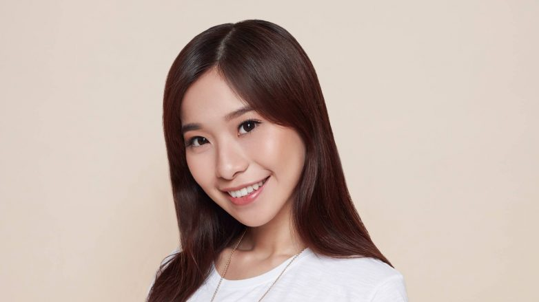 Remedies for dry hair: Asian woman with long dark hair wearing a white shirt smiling