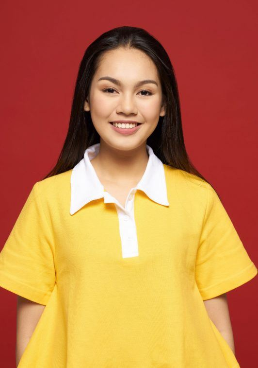 Rope braid: Asian girl with long black hair wearing a yellow shirt against a red background