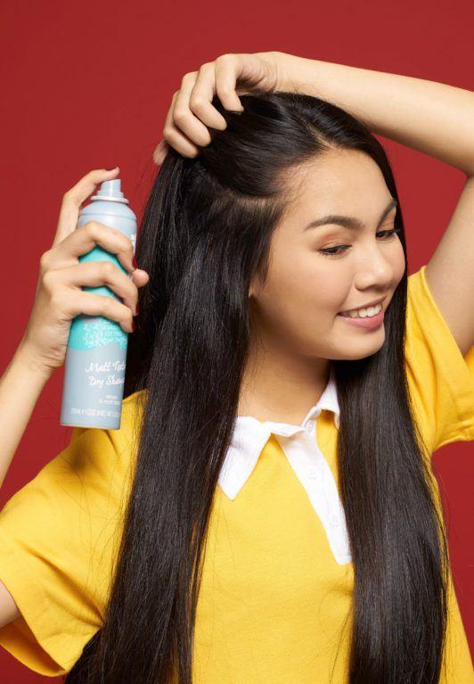 Rope braid: Closeup shot of an Asian woman with long black hair wearing a yellow shirt spraying dry shampoo on her hair