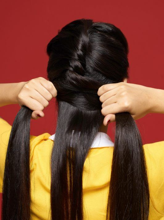 Rope braid: Back shot of Asian woman braiding her long black hair against a red background