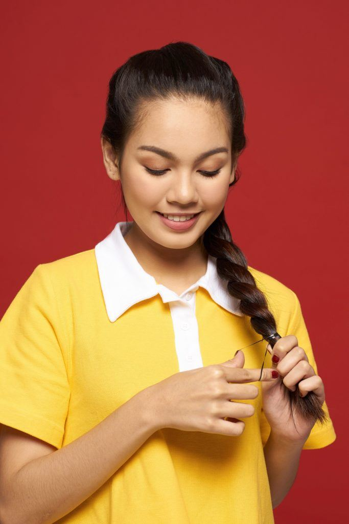 Rope braid: Closeup shot of an Asian woman with long black hair wearing a yellow shirt braiding her hair
