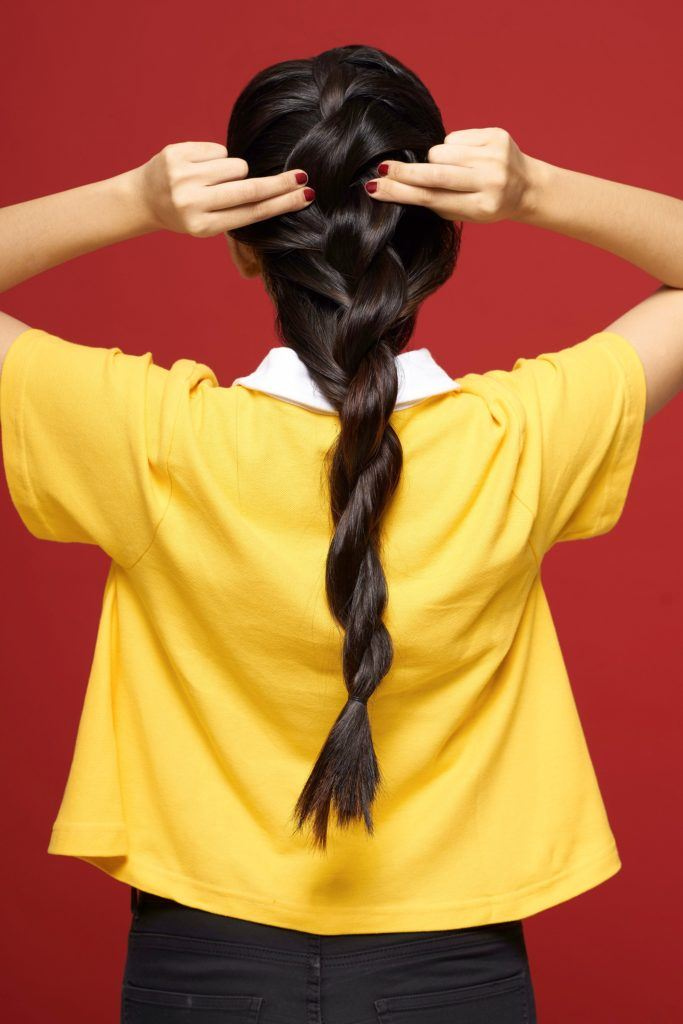 Rope braid: Back shot of an Asian woman with long black hair wearing a yellow shirt fixing her braid