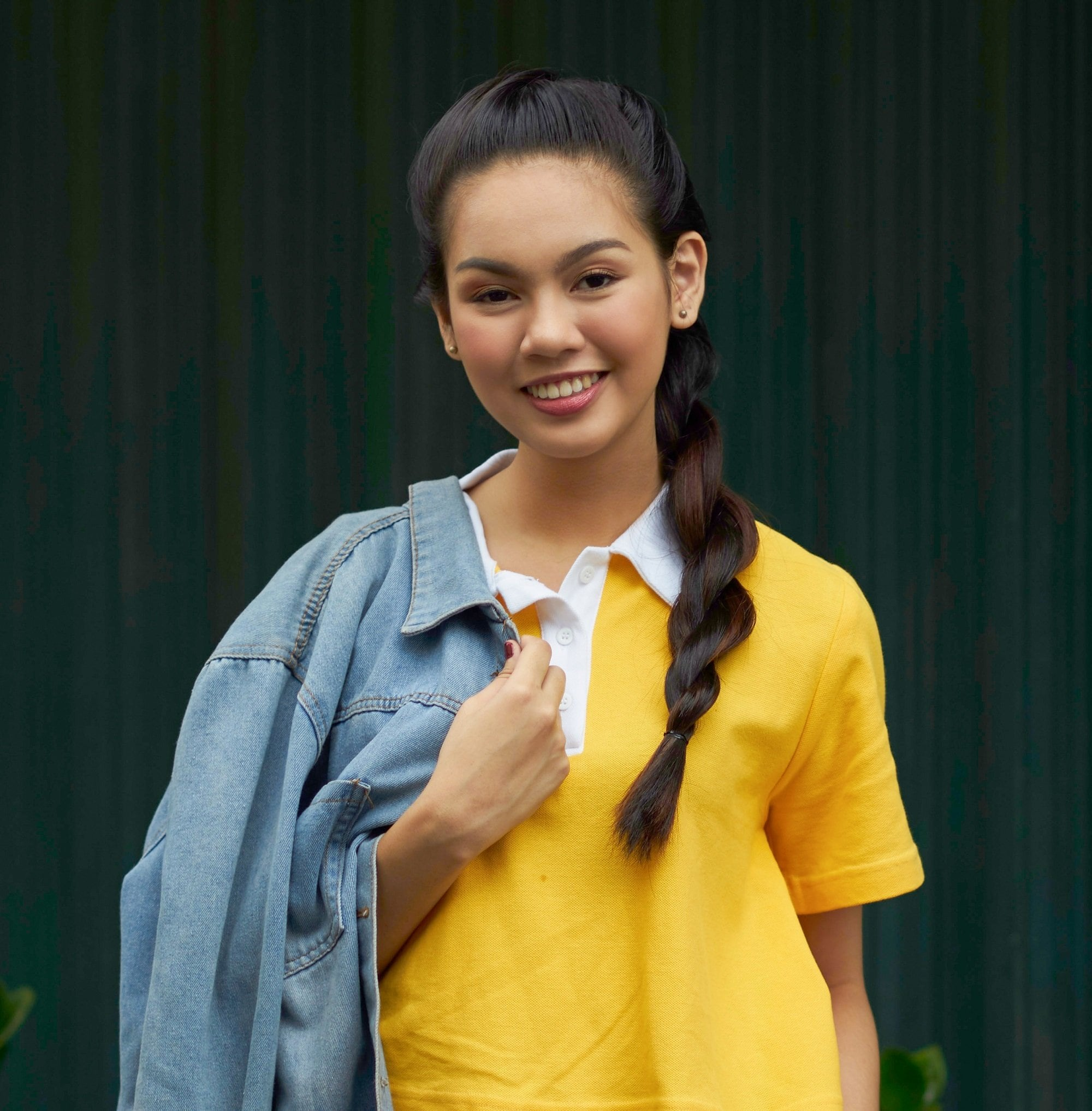 Asian woman with long black hair in a rope braid wearing a yellow shirt outdoors