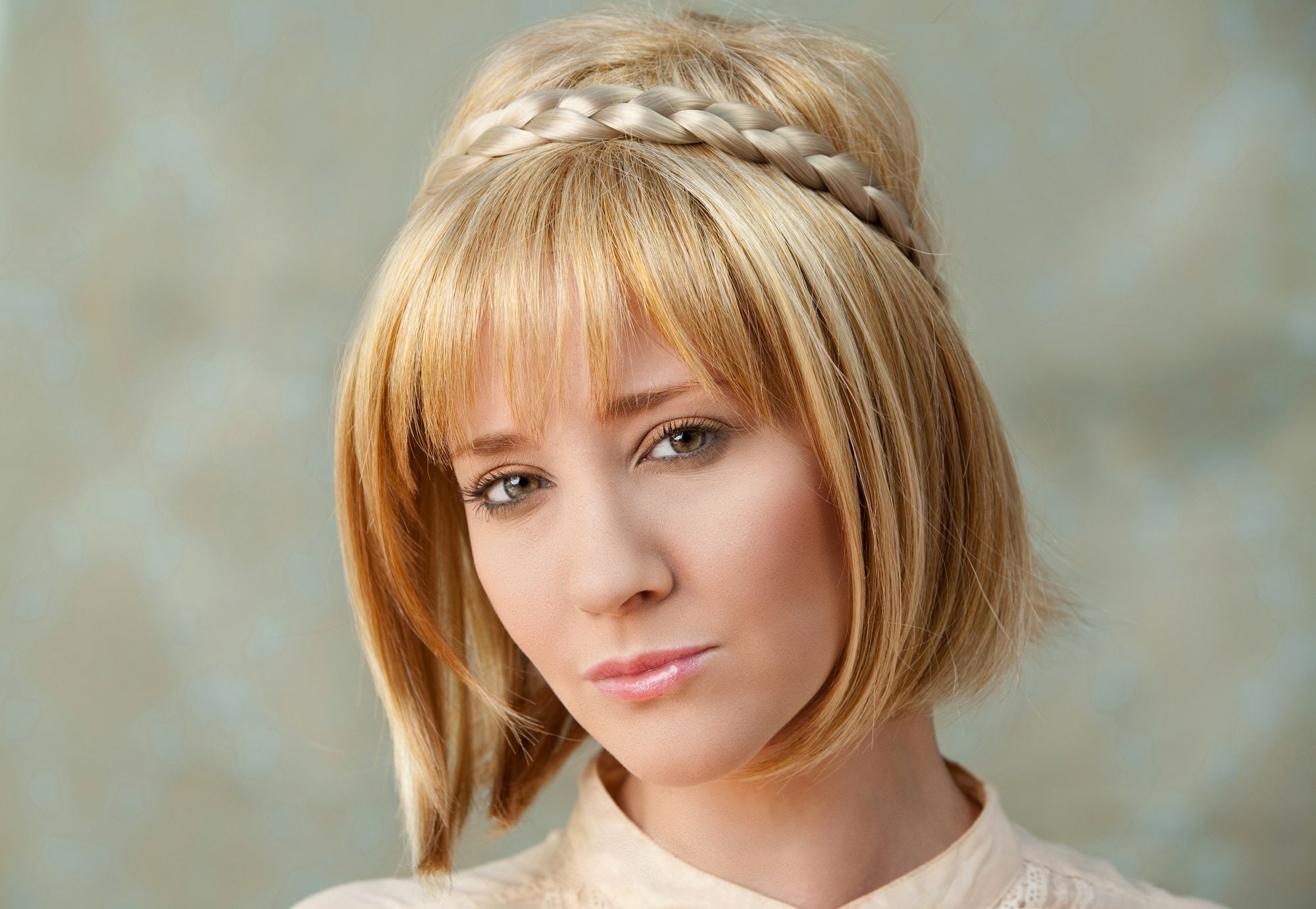 Short blonde hair: Closeup shot of a woman wearing beige top with blonde bob with bangs