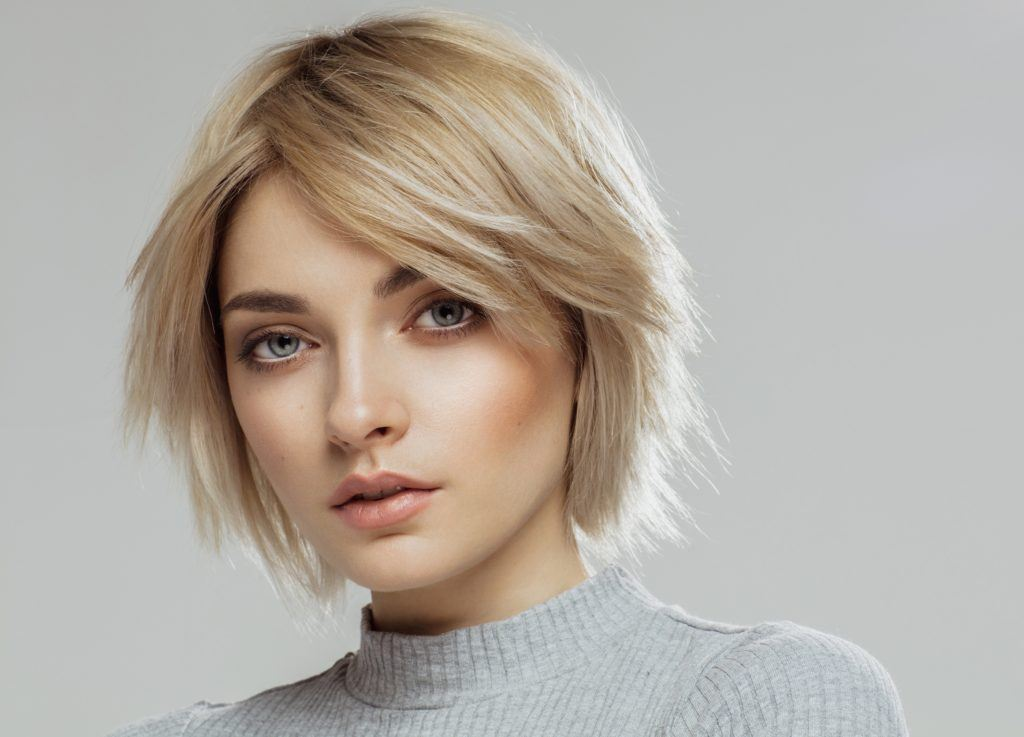 Haircuts for rainy season: Closeup shot of a woman with short layered blonde hair wearing a gray top against a gray background