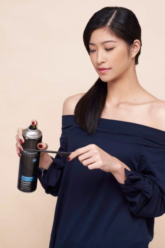 Side ponytail: Asian woman wearing a dark blue blouse spritzing hairspray on a comb