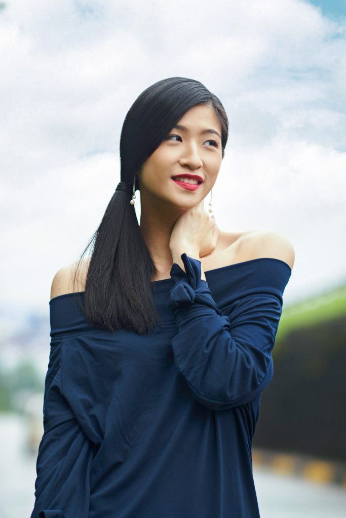 Side ponytail: Asian woman wearing darl blue blouse with long black hair in side ponytail in outdoor location