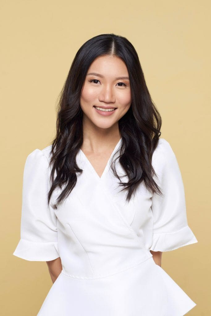 Asian woman with long black hair wearing a white blouse against a yellow background