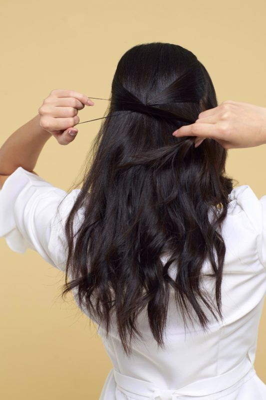 Twisted ponytail half updo: Back shot of Asian woman tying her long black hair wearing a white blouse