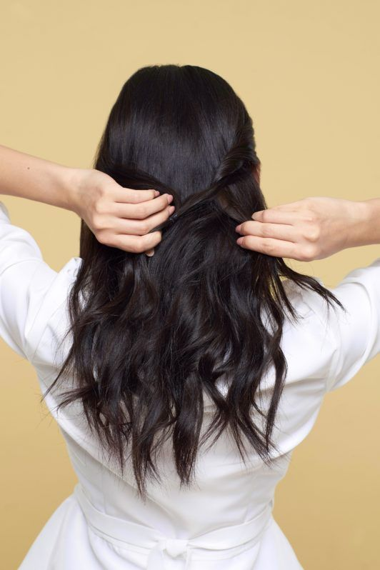 Twisted ponytail half updo: Back shot of Asian woman styling her long black hair wearing a white blouse