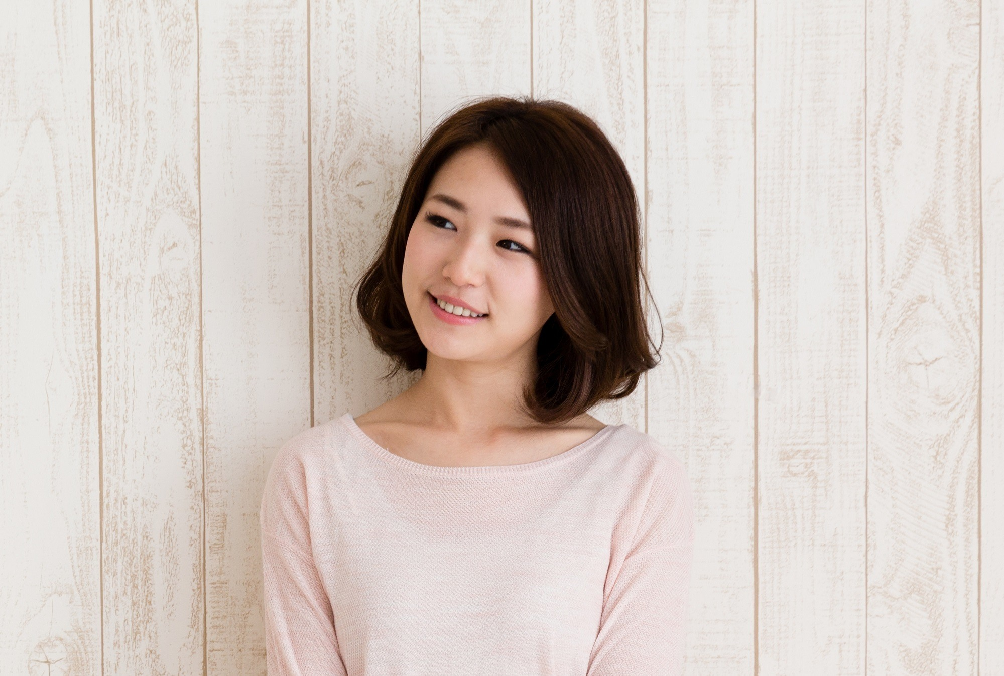 Best haircuts for different face shapes: Closeup shot of an Asian woman with dark lob wearing a light pink sweater