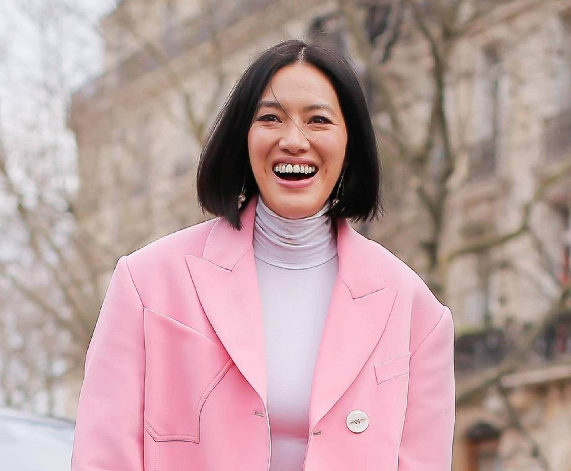 Best haircuts for different face shapes: Closeup shot of a woman with straight black lob wearing a pink blazer outdoors