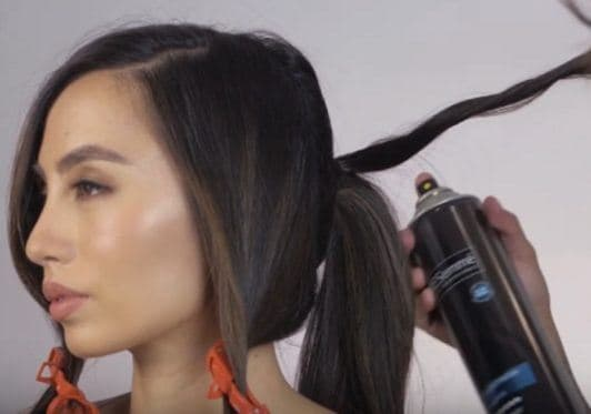 Chic twisted ponytail: Filipina woman Martine Cajucom putting her long black hair into a ponytail and being sprayed