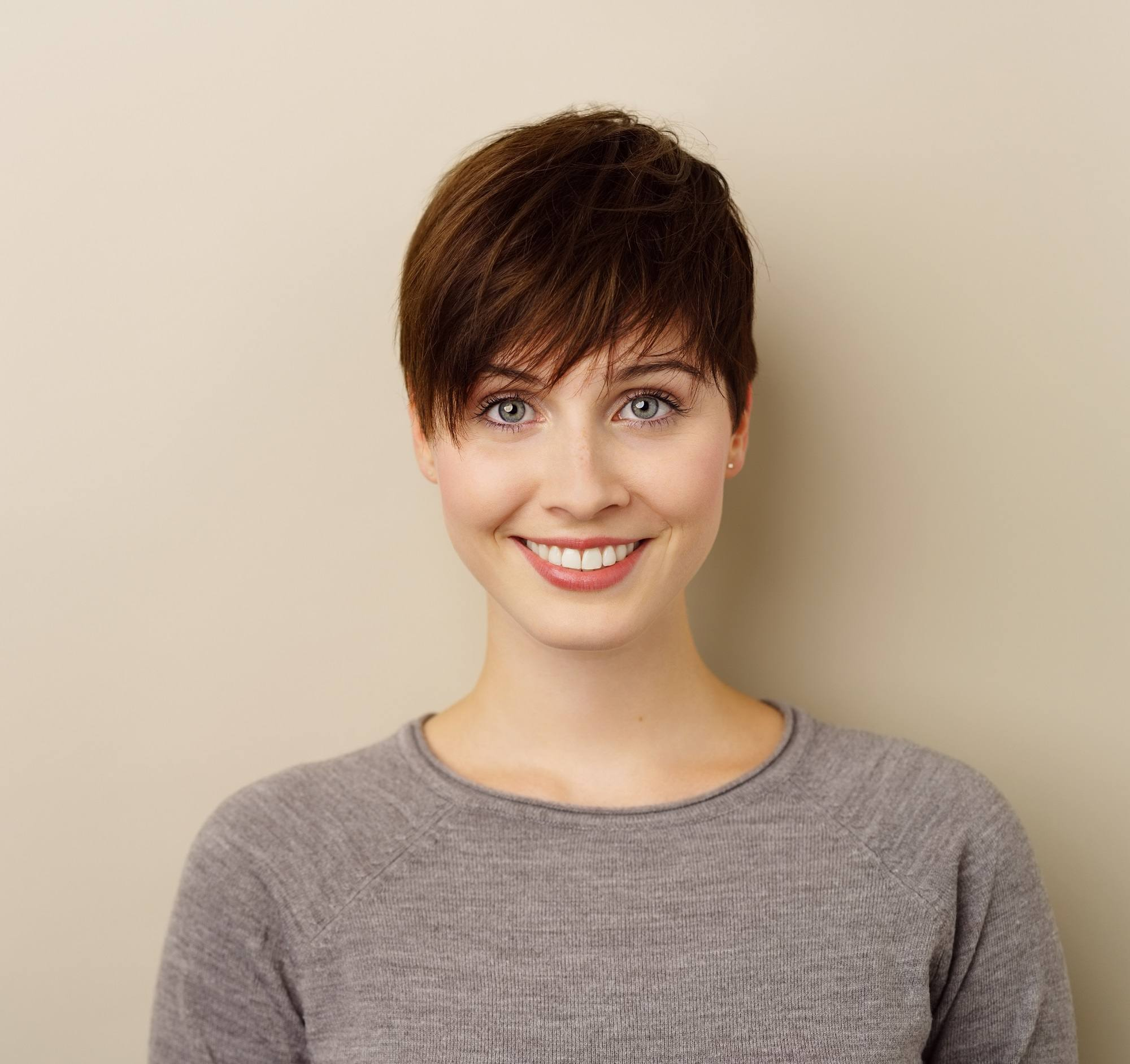 Chocolate brown hair color: Closeup shot of a woman with short dark brown pixie cut wearing a gray shirt against a pale beige background