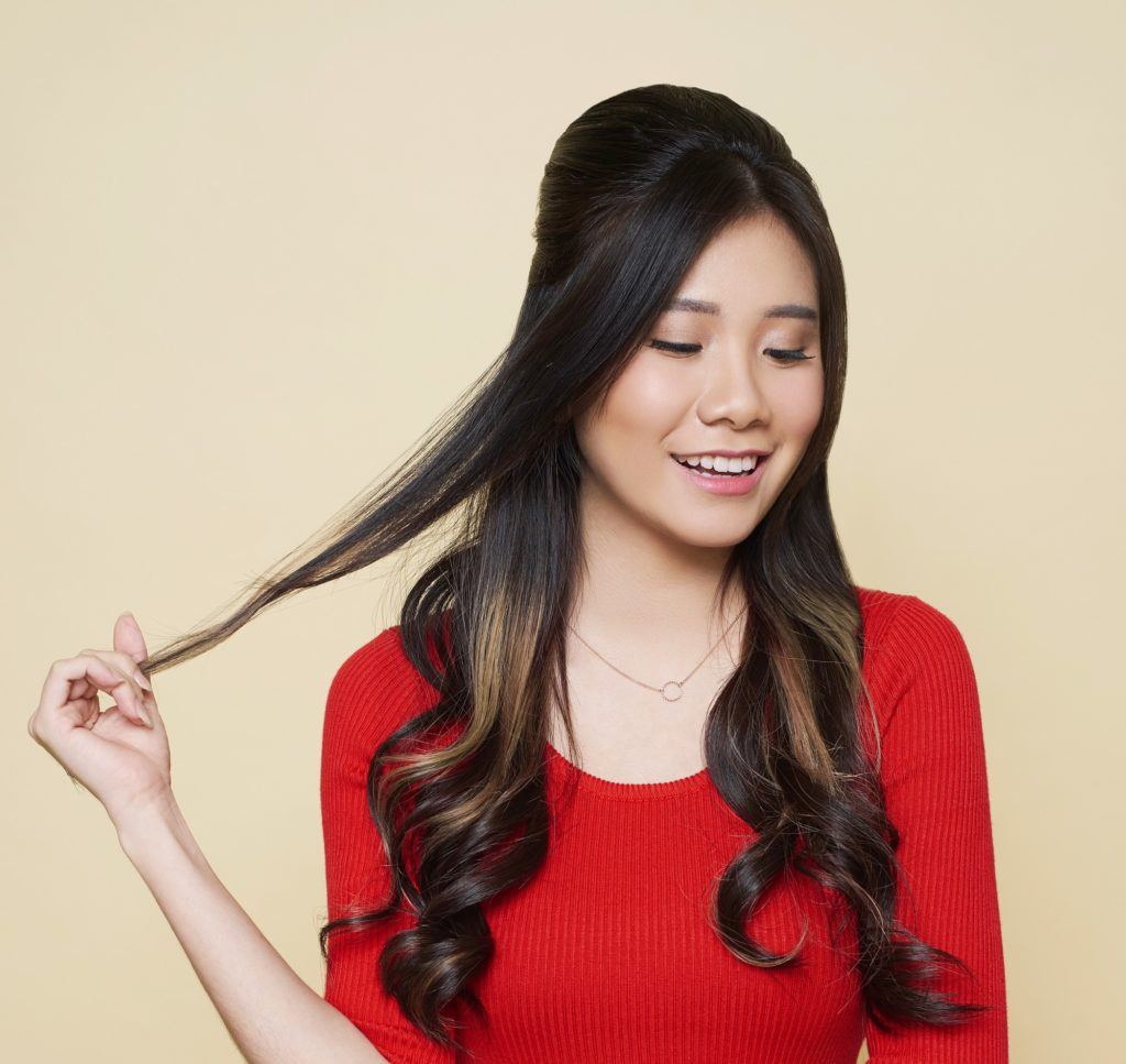 Christmas party hairstyles: Closeup shot of an Asian woman with long dark hair in beehive hairstyle wearing a red dress