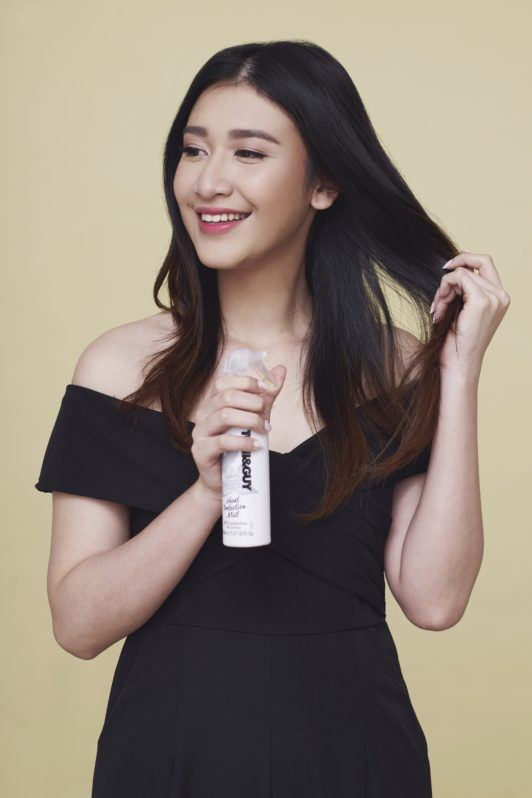 Cream Silk Triple Keratin Rescue Sexy Romantic Waves: Asian woman spraying heat protectant on her long dark hair