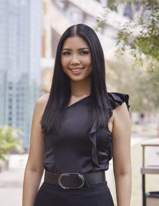 Cream Silk Triple Keratin Rescue Ultimate Straight Glamorously Straight Hair: Asian woman with long black straight hair and wearing black top and skirt in a city park