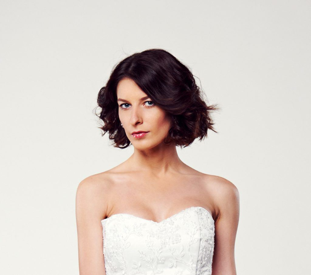 Elegant hairstyles for short hair: Closeup shot of a woman with short black hair wearing a white tube dress