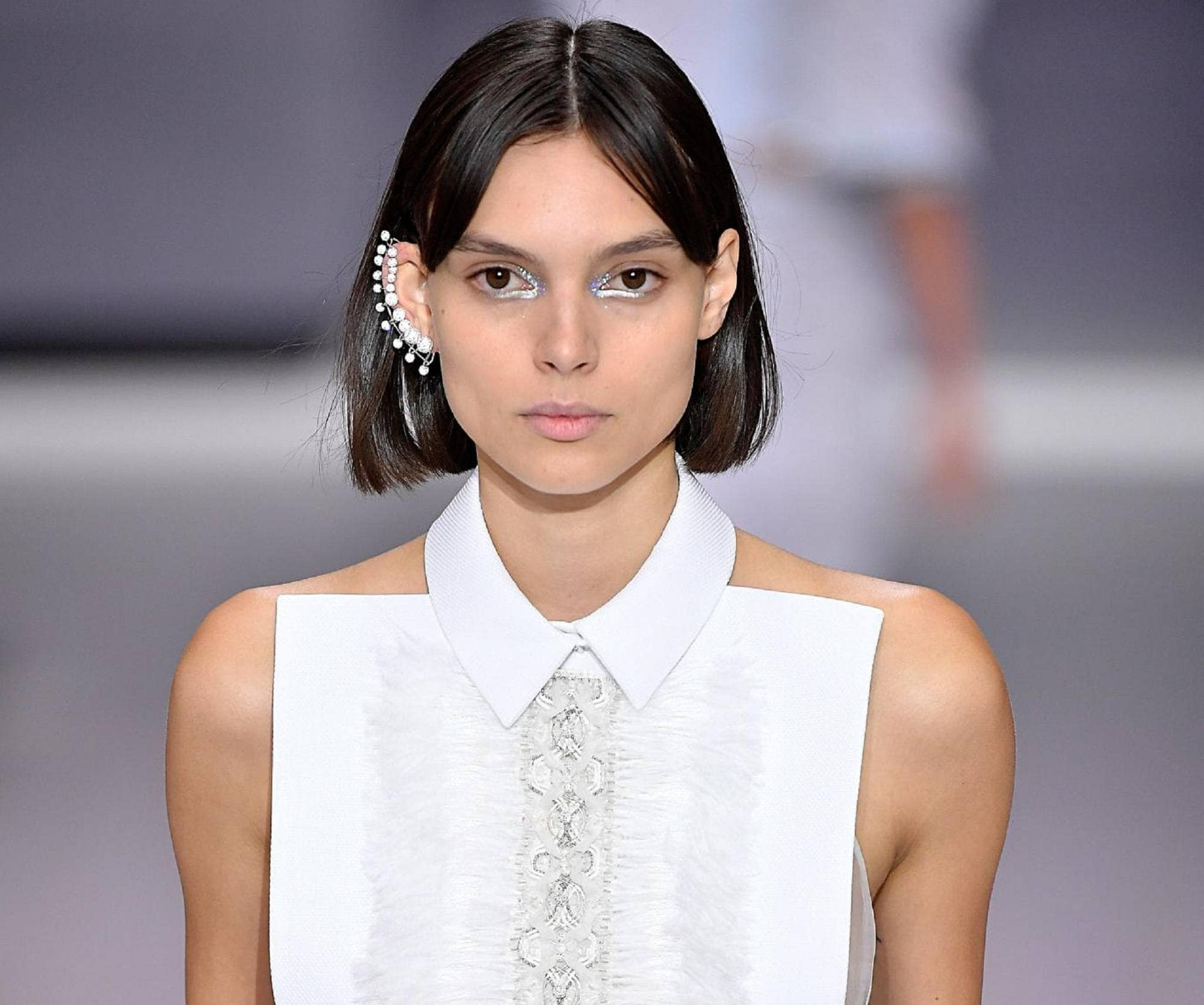 Elegant hairstyles for short hair: Closeup shot of a woman with straight black bob wearing white