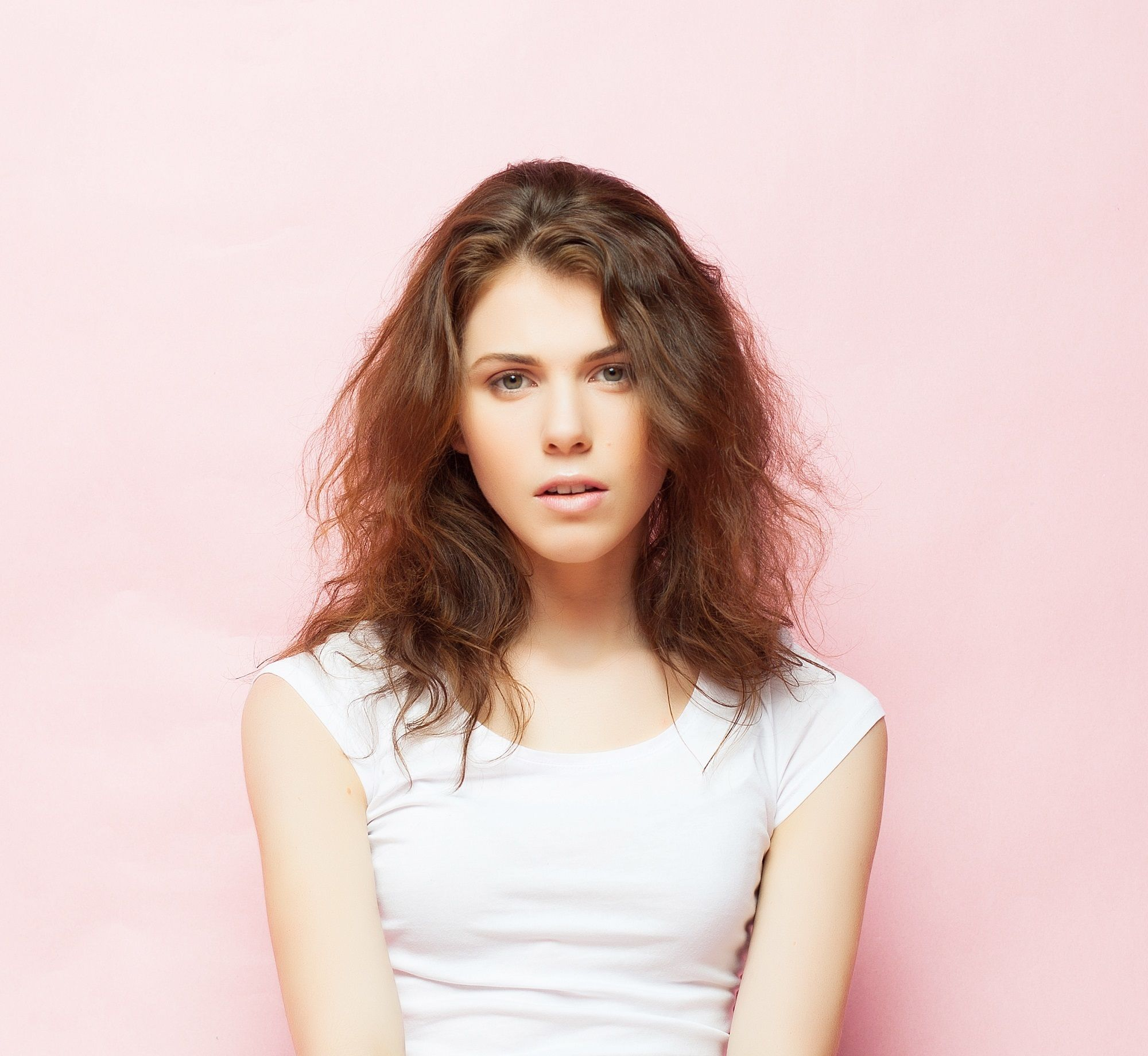 Frizzy hairstyles: Closeup shot of a woman with messy brown hair against a pink background