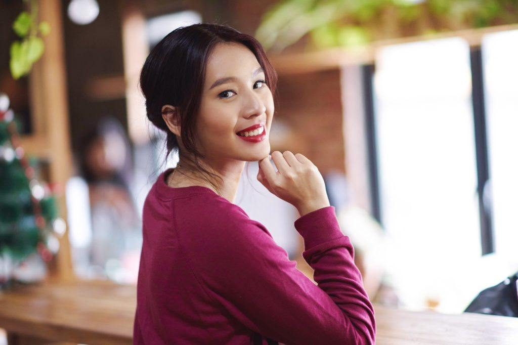 Get the look holiday hairstyles: Closeup shot of an Asian woman with black hair in a banana bun wearing fuchsia sweater in a cafe