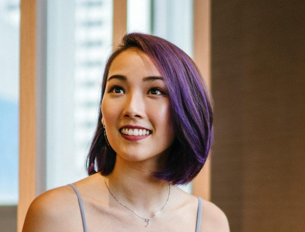 Highlights for dark hair: Closeup shot of an Asian woman with bob with purple highlights wearing a spaghetti-strapped top indoors