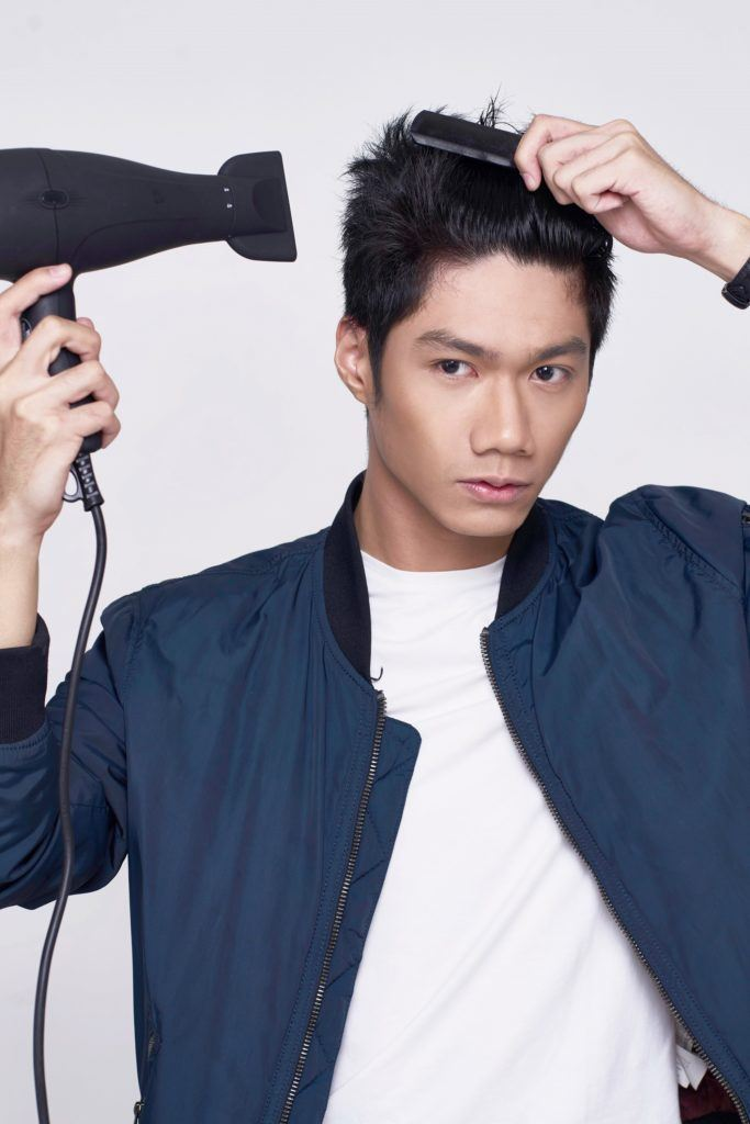 How to style short hair for men: Asian man blow drying her short black hair wearing a blue jacket and white shirt