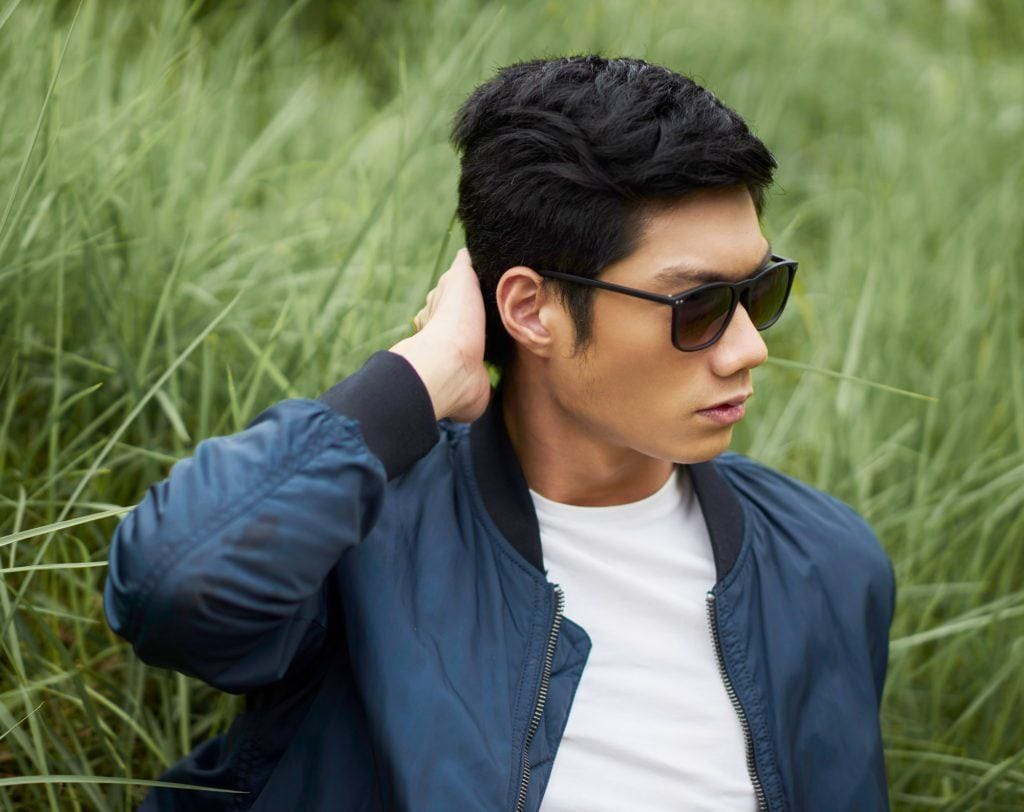 How to style short hair for men: Closeup shot of an Asian man with short black hair wearing shades and blue jacket and white shirt sitting on the grass