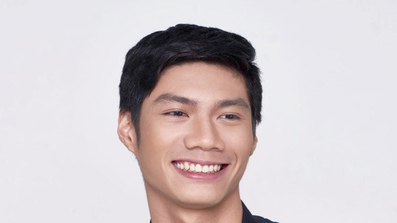 How to style short hair for men: Closeup shot of Asian man with short black hair smiling wearing a blue jacket and white shirt