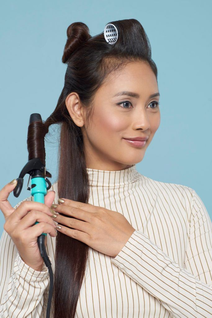 Long hair with curly side fringe: Asian woman starting to curl her long dark hair