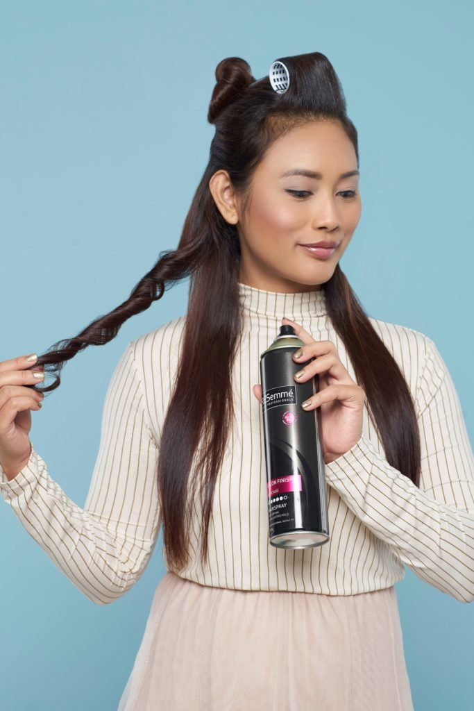 Long hair with curly side fringe: Asian woman spritzing hairspray on her long dark hair