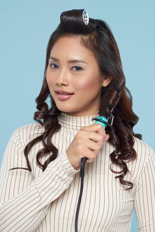 Long hair with curly side fringe: Asian woman curling her long dark hair wearing a white turtleneck top
