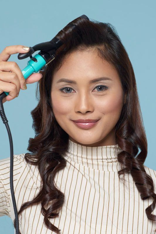 Long hair with curly side fringe: Asian woman with long dark wavy hair curling her side fringe