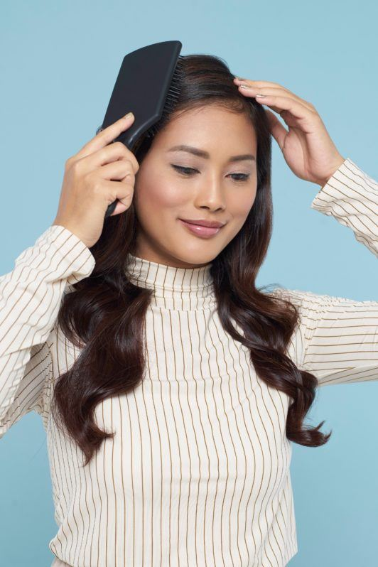 Long hair with curly side fringe: Asian woman brushing her long dark wavy hair wearing a white top