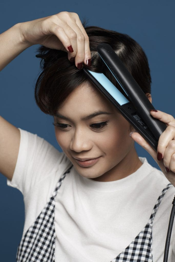 Messy textured pixie cut: Closeup shot of Asian woman ironing her short black pixie cut