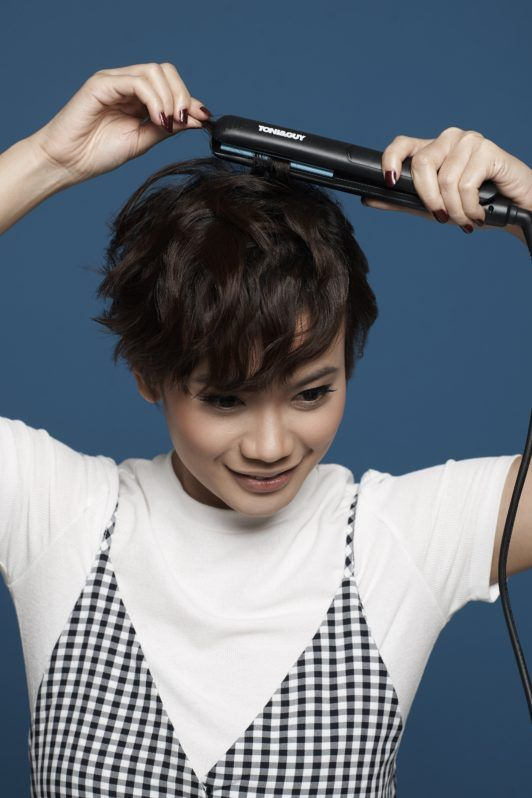 Messy textured pixie cut: Closeup shot of an Asian woman ironing her black pixie cut