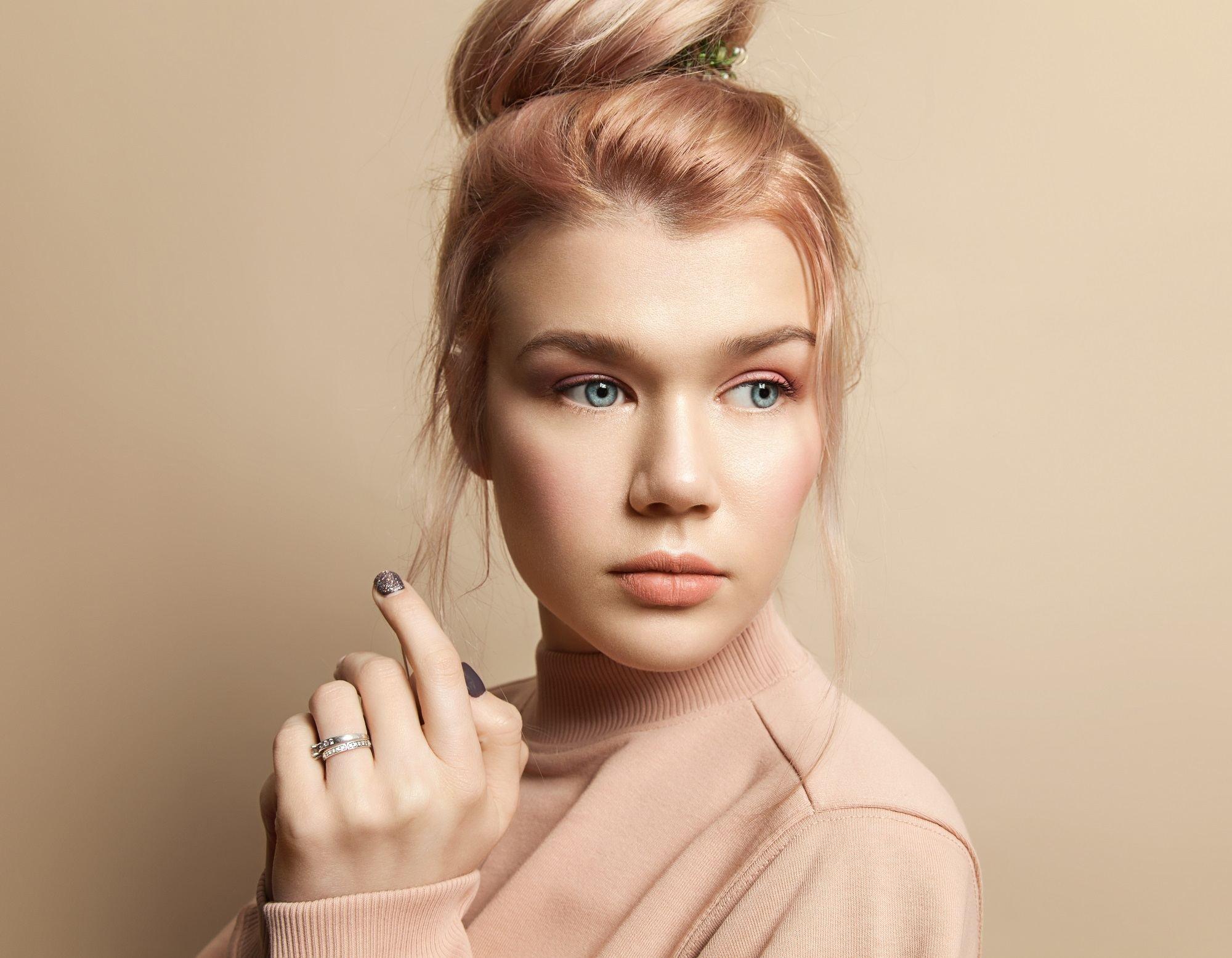 Peach hair: Closeup shot of a woman with peach hair in a top bun wearing a peach shirt