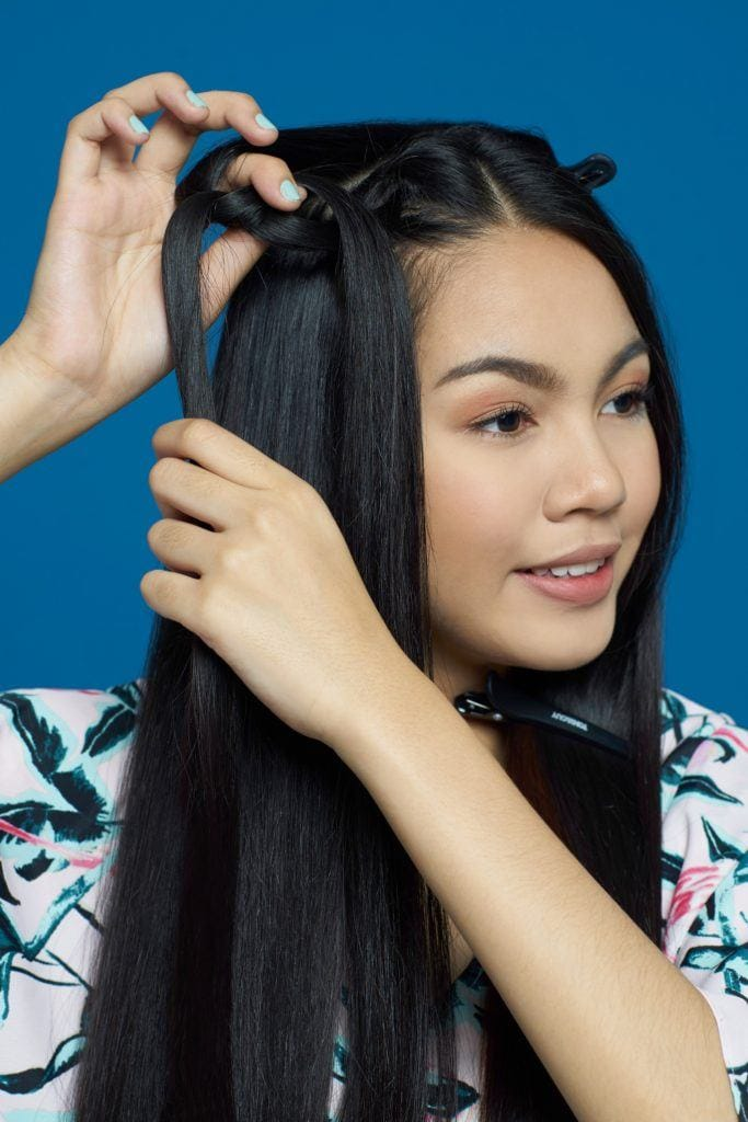 Pipe braids: Asian woman styling her long black hair against a blue background