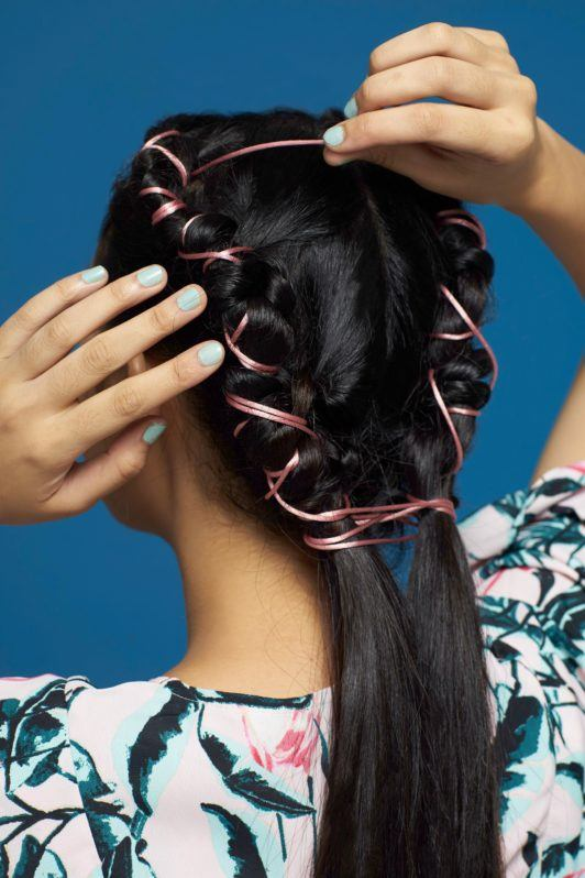 Pipe braids: Back shot of Asian woman styling her long black hair against a blue background