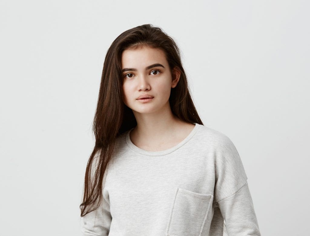 Shampoo for thick hair: Woman with long dark brown hair wearing a white long-sleeved shirt