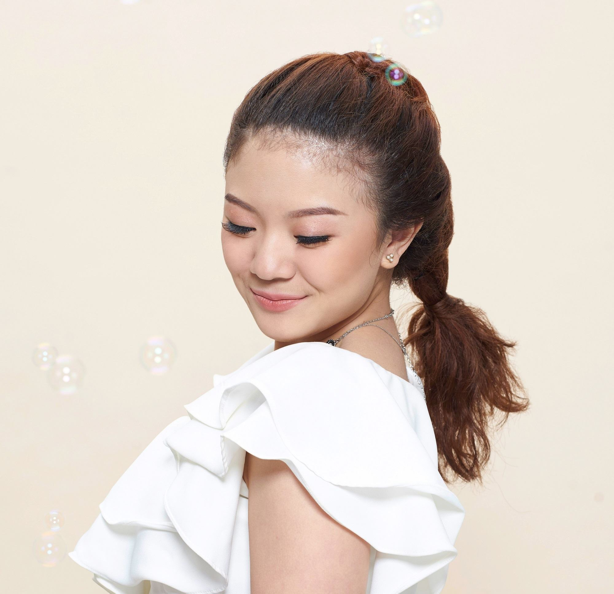 Shampoo for thick hair: Closeup shot of Asian woman with long brown hair in pull through braid wearing a white blouse