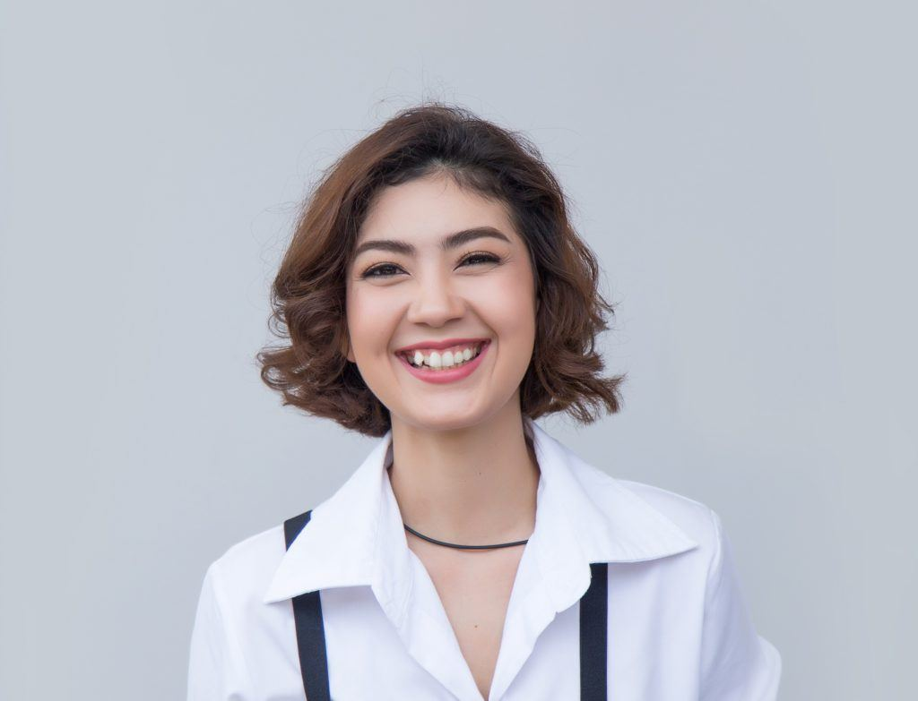 Wavy bob: Closeup shot of a woman with wavy brown bob wearing a white collared blouse
