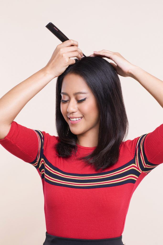 Asian woman parting her shoulder length black hair using a tail comb