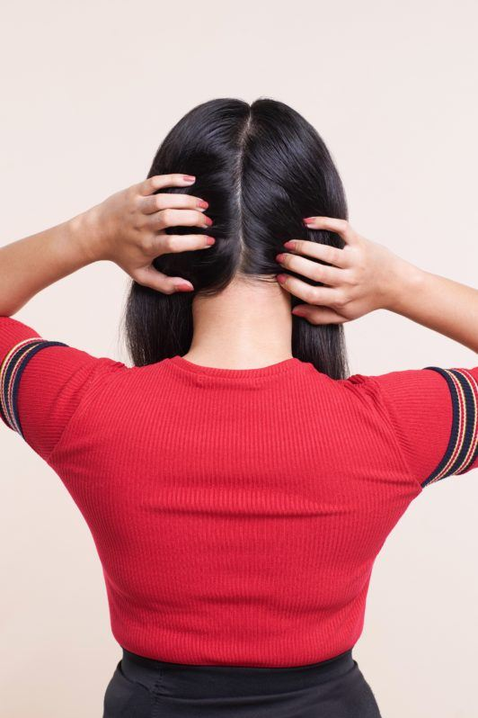 Crown braid: Back shot of an Asian woman dividing her shoulder length black hair into two vertical sections