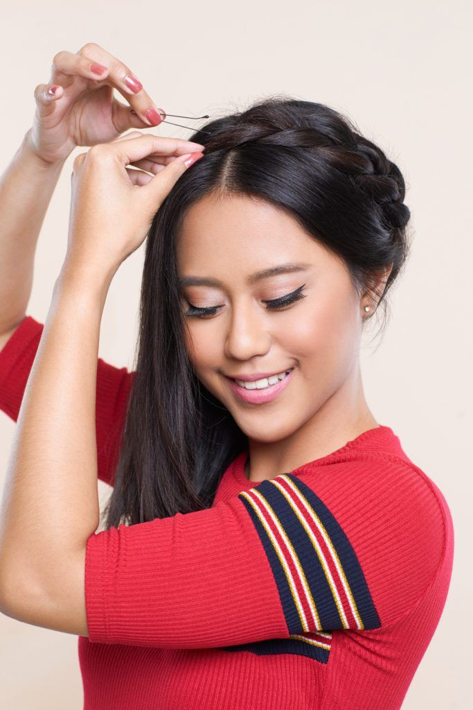 Crown braid: Asian woman with shoulder length dark hair pinning her braid on top of her head