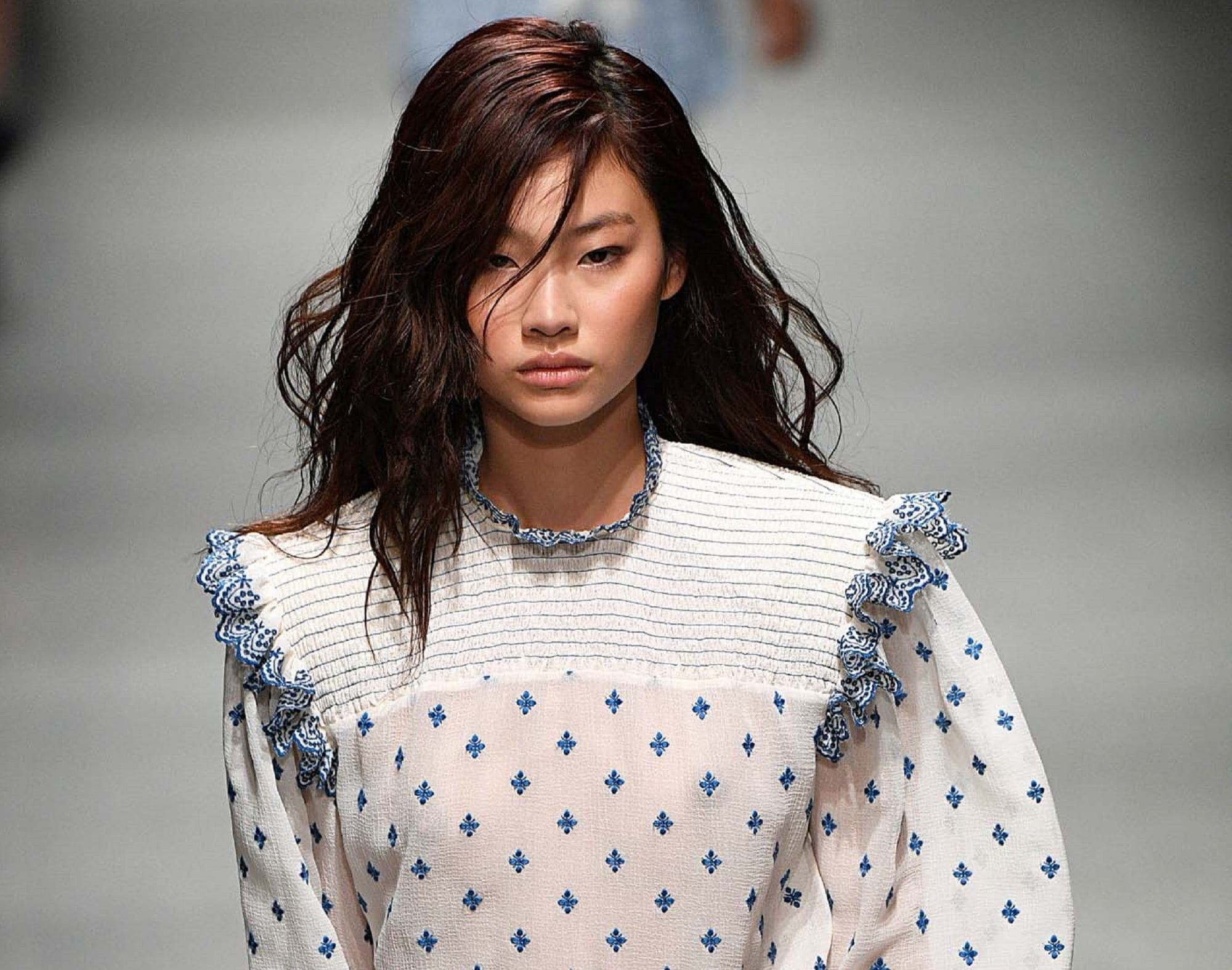 Dark brown hair color: Closeup shot of an Asian woman with deep chocolate hair wearing a white polka dotted dress walking in a fashion show