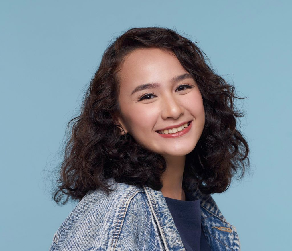 Haircuts for thick hair: Closeup shot of an Asian woman with shoulder length thick hair wearing a denim jacket