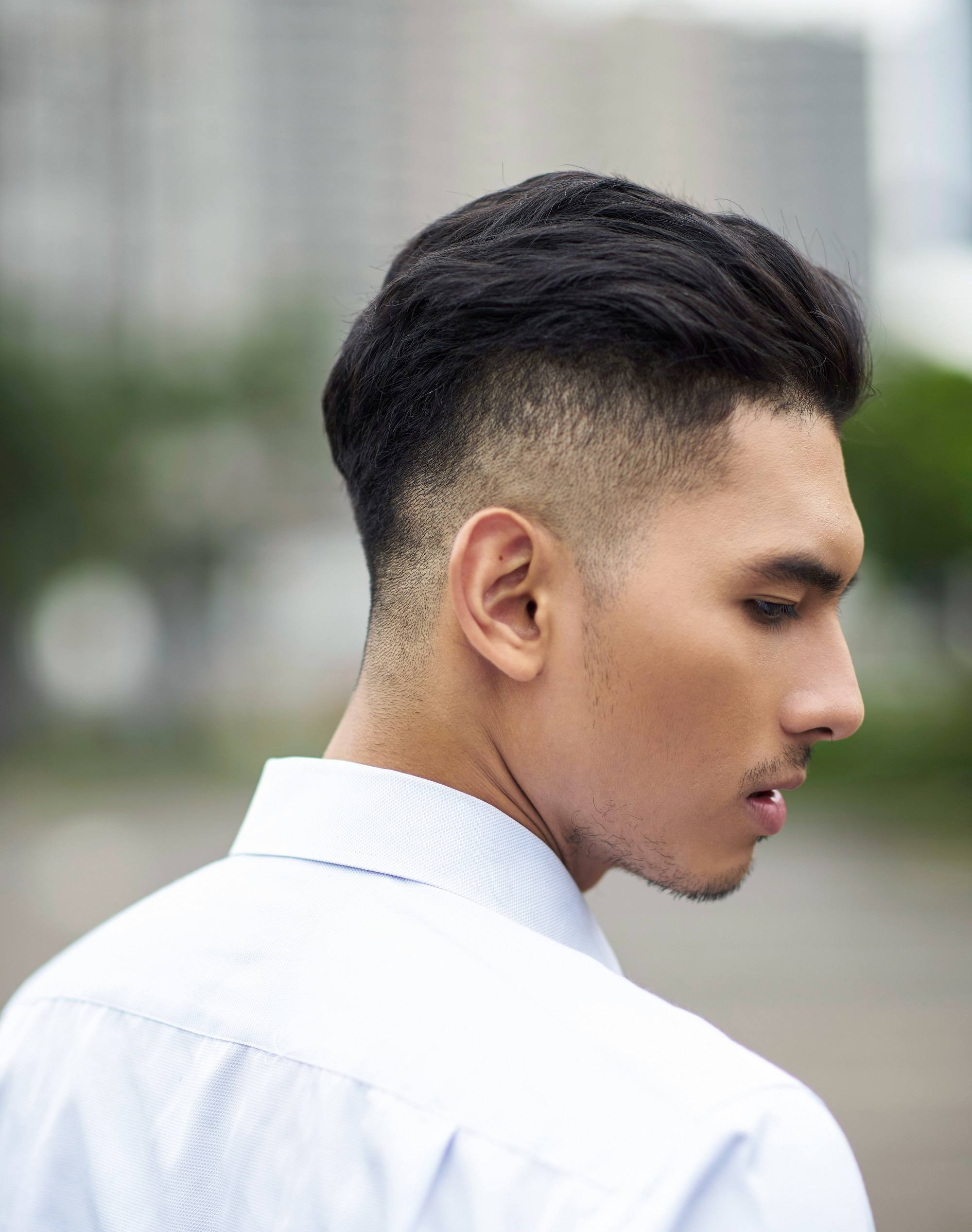 Healthy scalp: Closeup side view of an Asian man with shaved side hairstyle outdoors