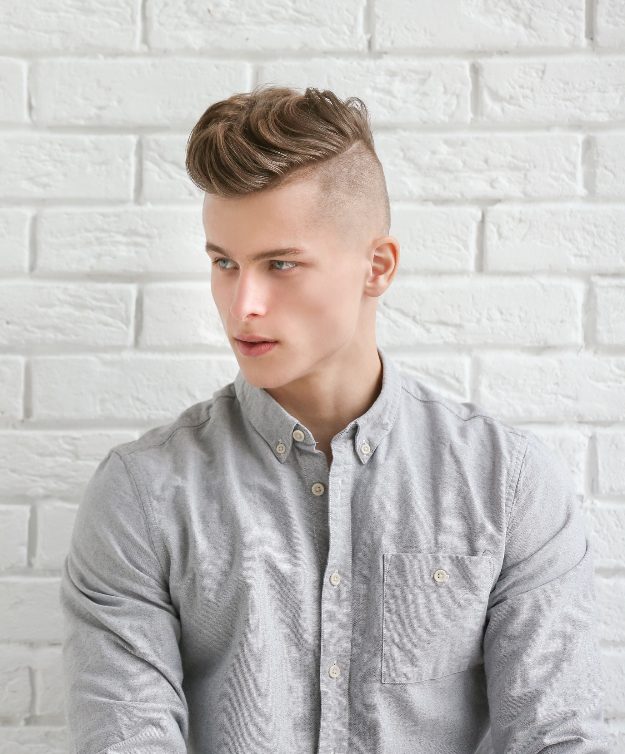 Healthy scalp: Closeup shot of a Caucasian man with shaved sides and brown hair in pompadour hairstyle