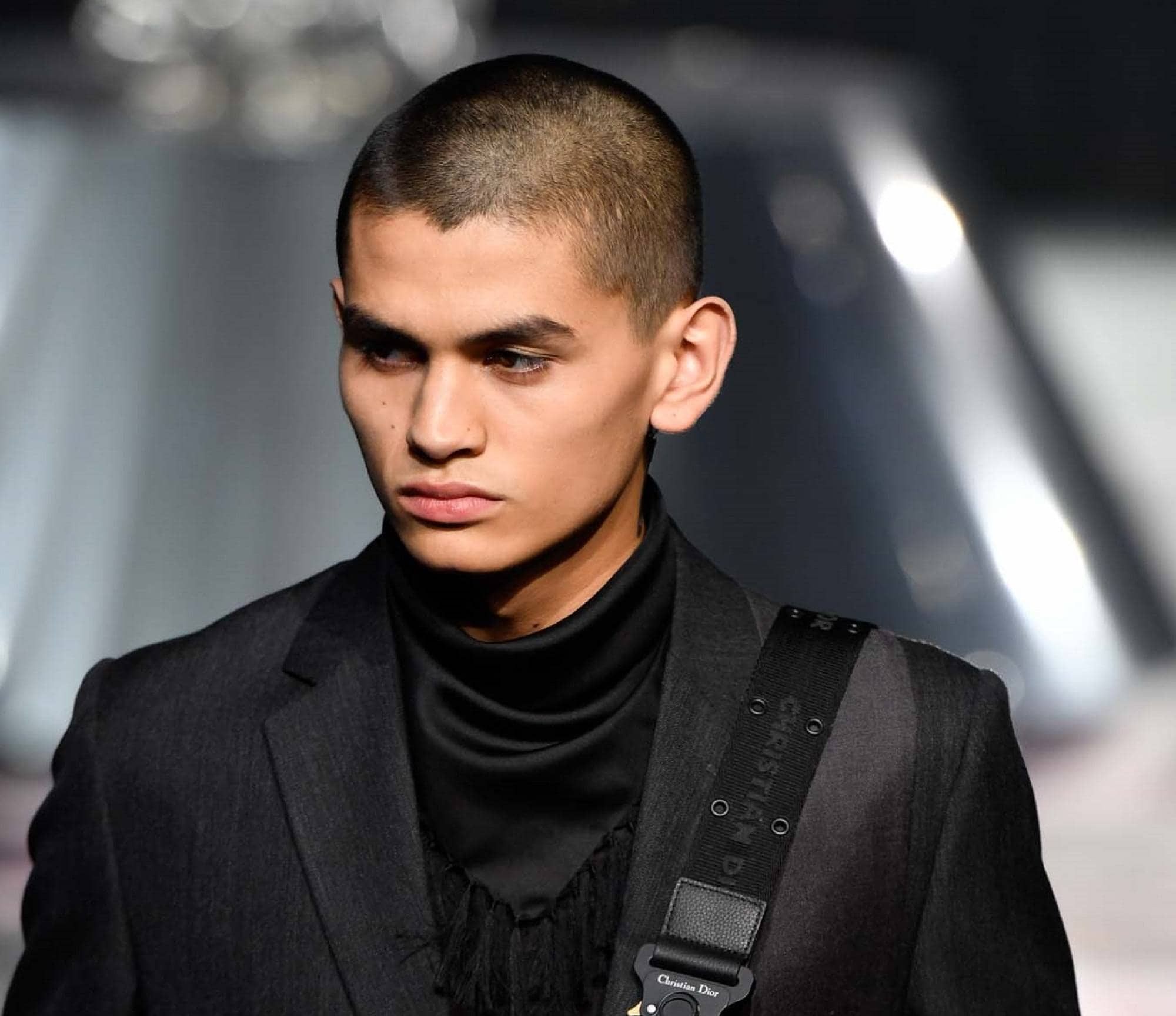 Healthy scalp: Closeup shot of a semi-bald man wearing a black suit on the runway